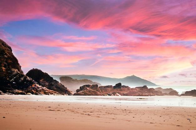 Strand omgeven door rotsen en de zee onder een bewolkte hemel tijdens een prachtige roze zonsondergang Gratis Foto