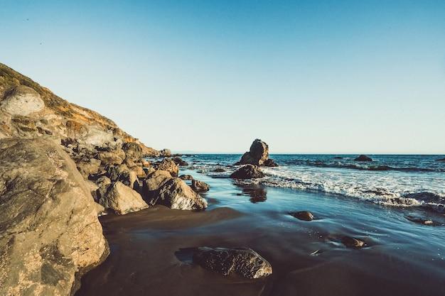 Strandgolven die de kust met rotsen op een zonnige dag in marin, californië raken Gratis Foto