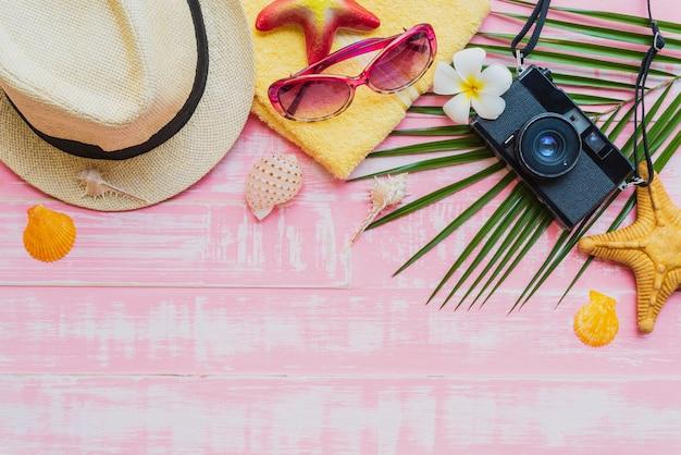 Strandtoebehoren op heldere roze pastelkleur houten achtergrond Premium Foto