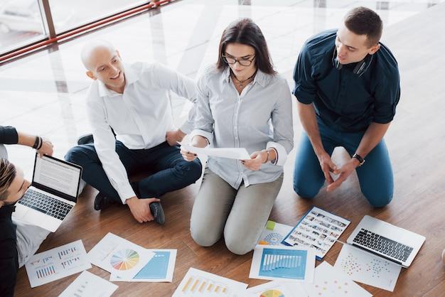 Strategie samen plannen. commercieel team die documenten op vloer met manager bekijken die aan één idee richten. samenwerking bedrijfsprestaties. planning ontwerp tekenen. teamwerk concept Premium Foto