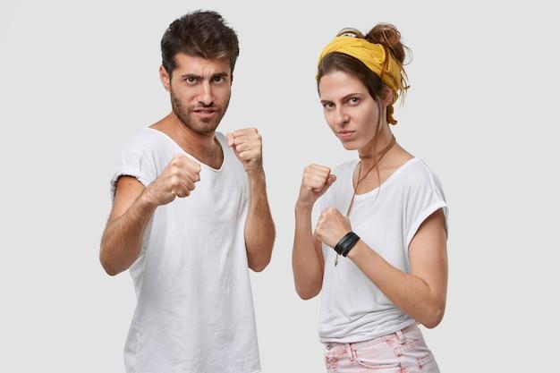 Strenge mooie dame en haar ongeschoren vriend staan samen, houden de handen in een defensief gebaar, zien er serieus uit, klaar om te vechten en zichzelf te beschermen, poseren tegen een witte muur Gratis Foto