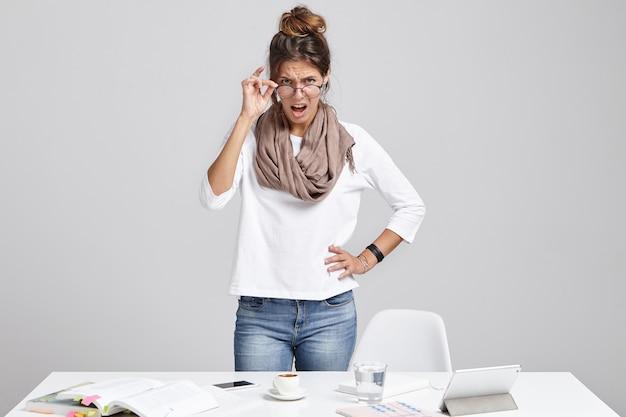 Strenge vrouwelijke baas, kijkt boos door een bril, gaat schreeuwen Gratis Foto