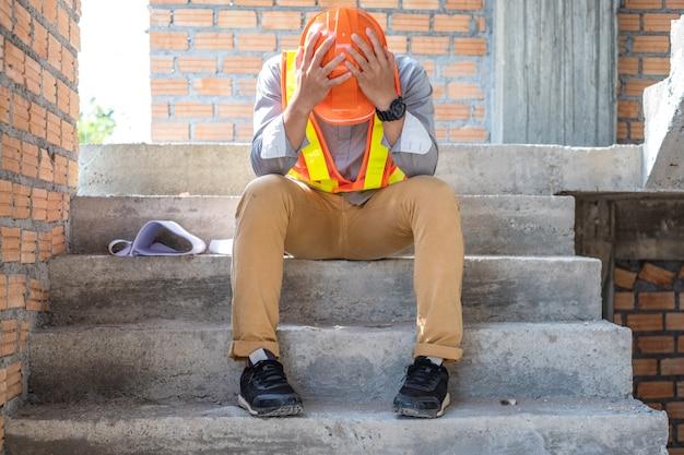 Stress ingenieur of architect hand in hand op zijn hoofd. hij heeft problemen op het werk. hij zit op trappen. engineering concept. Premium Foto