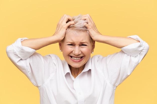 Stress, problemen, woede, woede en negatieve emoties. gefrustreerde wanhopige rijpe vrouw die schreeuwt en haar aftrekt, boos is op mislukking, gestrest door financiële problemen, haar geduld verliest Gratis Foto