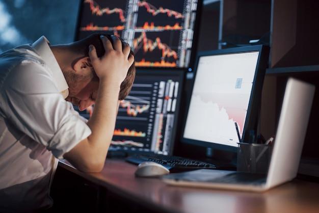 Stressvolle dag op kantoor. de jonge handen van de zakenmanholding op zijn gezicht terwijl het zitten bij het bureau in creatief bureau. beurs handel forex grafische financiën Premium Foto