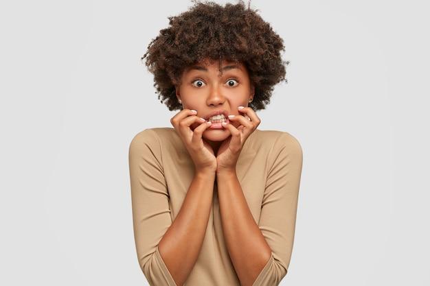Stressvolle emotionele jonge vrouw houdt handen in de buurt van mond Gratis Foto