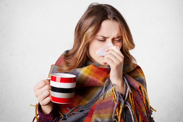 Stressvolle jonge mooie vrouw niest in servet, heeft lopende neus, drinkt warme drank, gewikkeld in plaid, lijdt aan kou, geïsoleerd over wit Premium Foto