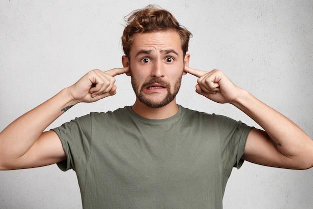 Stressvolle man met trendy kapsel, snor en baard pluggen oren, vermijdt harde geluiden Gratis Foto