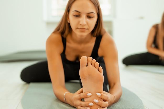 Stretching training. gezonde levensstijl. de jonge mooie vrouw in zwarte eenvormig doet uitrekkende oefening. akroyoga, yoga, fitness, training, sport. Premium Foto