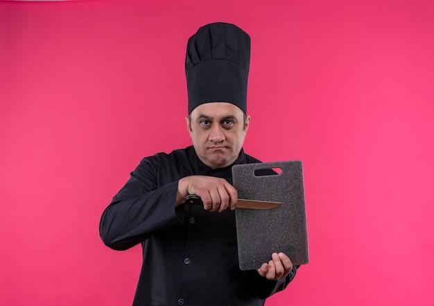 Strikte mannelijke kok op middelbare leeftijd in snijplank en mes van de chef-kok eenvormig bedrijf Gratis Foto