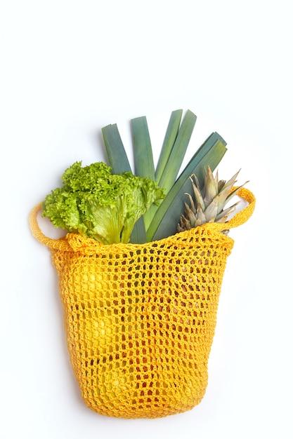 String katoenen tas met groene kruiden en fruit. verticaal beeld. het concept van natuurbehoud en afvalvrij. Premium Foto
