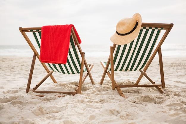 Strohoed en handdoek bleef strandstoelen Gratis Foto