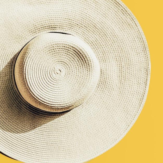 Strohoed op heldere gele zonnige achtergrond Gratis Foto