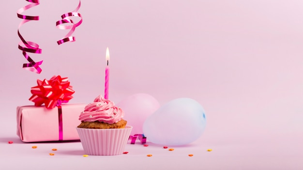 Strooi over de geschenkdoos; ballonnen en muffins met brandende kaars op roze achtergrond Gratis Foto