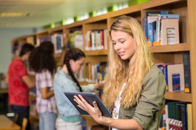 Student die digitale tablet in bibliotheek gebruikt Premium Foto