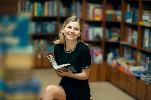 Student die een boek in de bibliotheek leest Premium Foto