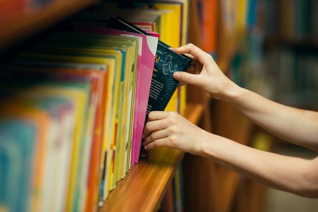 Student die naar boeken in een bibliotheek zoekt Premium Foto
