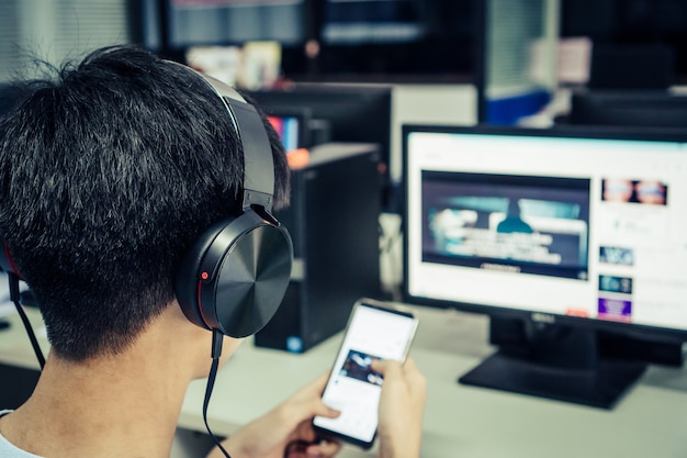 Student die online studieconcept leren: aziatische jonge mens die met hoofdtelefoons en laptop luistert Premium Foto