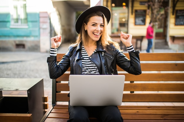 Student meisje zakenvrouw zitten op houten bankje in de stad in het park in de herfst Gratis Foto