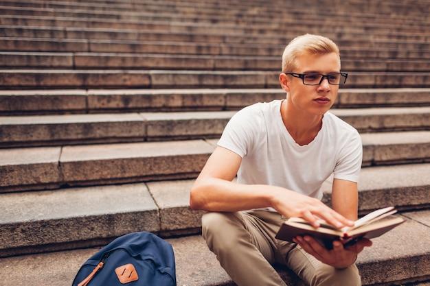 Student met rugzak lezen boek zittend op trappen en glazen te houden. guy studeert buitenshuis Premium Foto