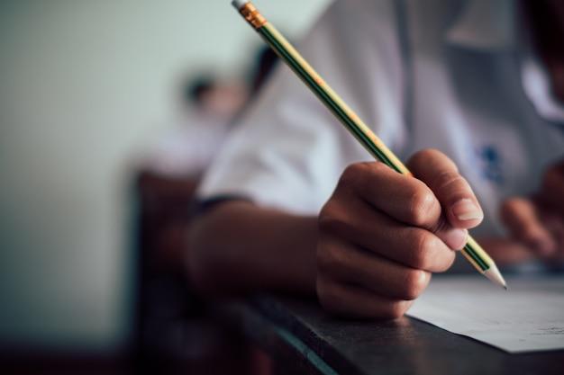 Student schrijven en lezen examen antwoordbladen in de klas van de school met stress Premium Foto