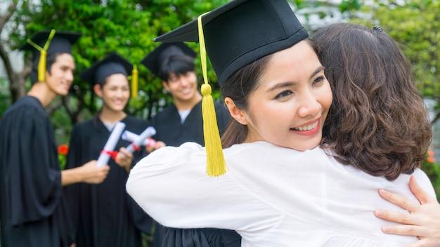 Studente met de afstuderen toga's en hoed knuffel de ouder in felicitatie ceremonie. Premium Foto