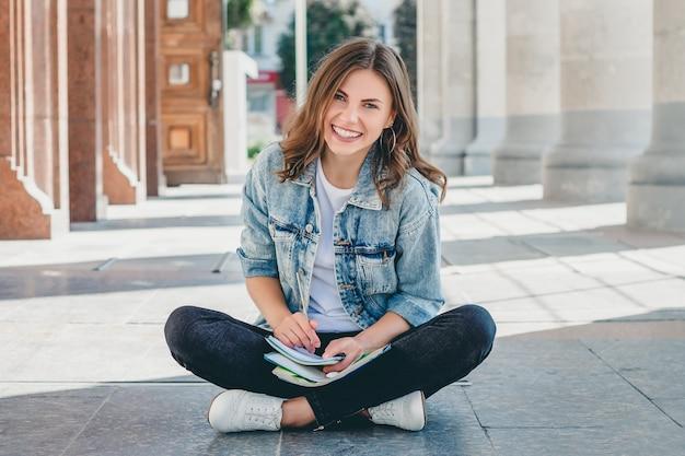 Studente zit tegenover de universiteit en glimlachen. leuke studente houdt pensil, mappen, notitieboekjes en lacht. meisje geeft lessen Premium Foto