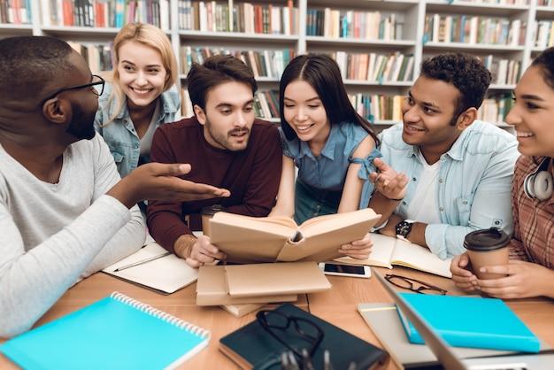 Studenten bespreken studeren in bibliotheek. Premium Foto