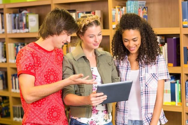 Studenten die digitale tablet in bibliotheek gebruiken Premium Foto