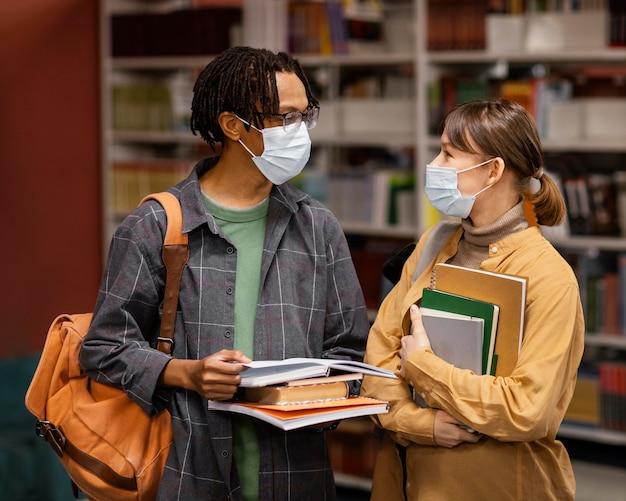 Studenten die medische maskers dragen in de bibliotheek Gratis Foto