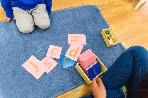 Studenten die montessori-materiaal verwerken in een school op een mat tijdens een les. Premium Foto