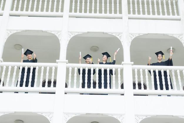 Studenten die zich gelukkig voelen met afstudeerjurken staan bij het ganggebouw. Premium Foto