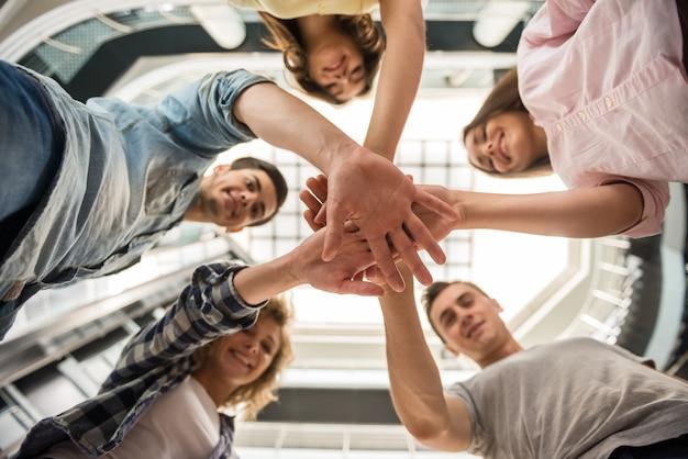 Studenten die zich in cirkel bevinden en handen samenbrengen. Premium Foto
