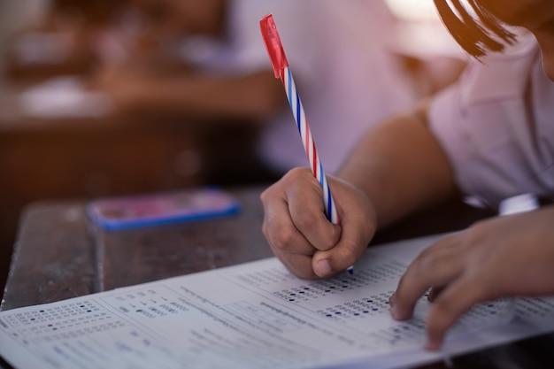 Studenten doen examen antwoordbladen oefeningen in de klas van de school met stress. Premium Foto