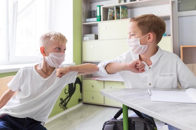 Studenten elleboog stoten in de klas Gratis Foto