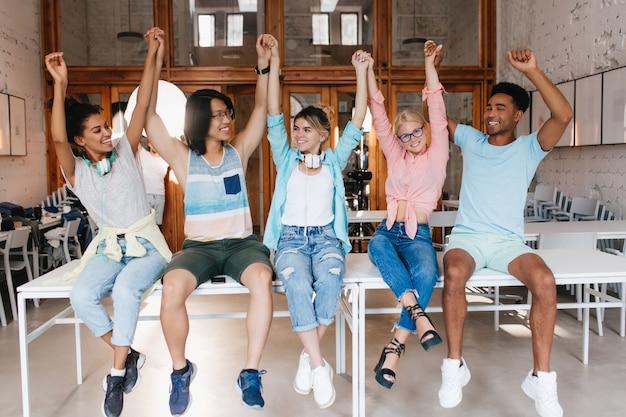 Studenten feliciteren elkaar met het einde van het schooljaar. universiteitsvrienden zijn blij dat ze geslaagd zijn voor het eindexamen en zwaaiende handen .. Gratis Foto