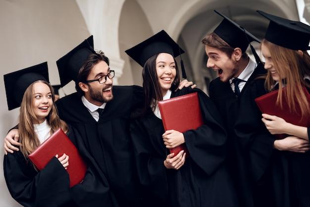 Studenten in mantels staan in de universitaire gang. Premium Foto