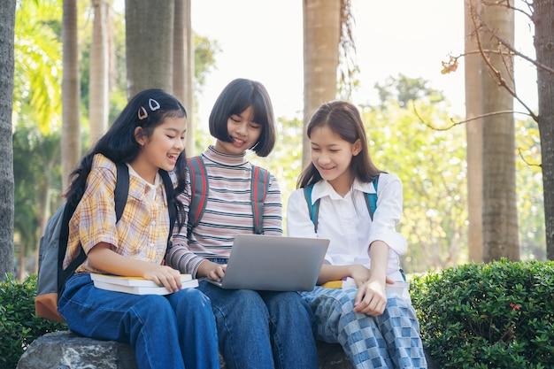 Studenten jonge aziaat die samen boekstudie lezen die met tablet, laptop computer op middelbare schoolcampus glimlachen, universiteit in de ontspanning van de de zomervakantie Premium Foto