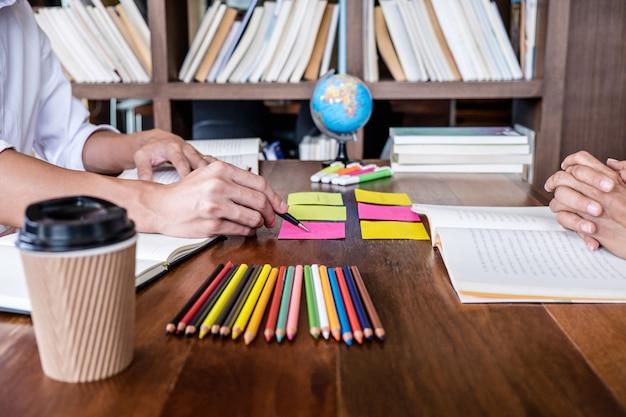 Studentencampus helpt een vriend bij het inhalen van een werkboek en bijles leren Premium Foto