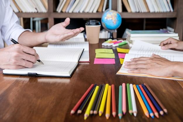 Studentencampussen of klasgenoten helpen een vriend bij het inhalen van een werkboek en bijles leren in de klas Premium Foto