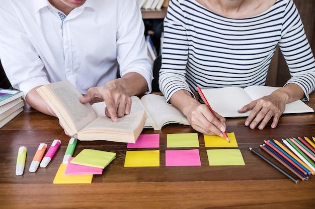 Studentengroepszitting bij bureau in en bibliotheek die, huiswerk en lespraktijk leest leest Premium Foto