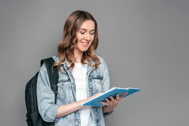Studentenmeisje die een notitieboekje met thuiswerk in haar en handen houden die lezen lezen geïsoleerd over grijze muurachtergrond Premium Foto
