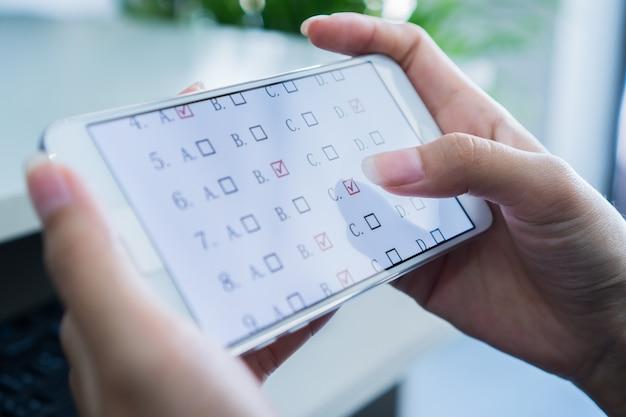 Studententest e-learningexamen op tabletcomputer met meerkeuzevragen door finge Premium Foto