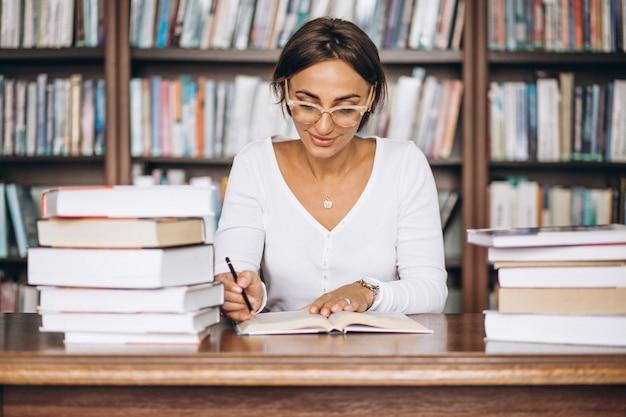 Studentenvrouw die bij de bibliotheek bestuderen Gratis Foto