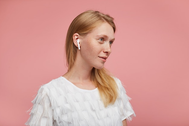 Studio foto van charmante jonge positieve roodharige dame gekleed in elegante kleding terwijl poseren op roze achtergrond met koptelefoon, vooruitblikkend en zacht glimlachend Gratis Foto