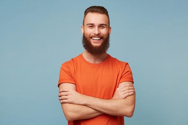 Studio portret van emotionele gelukkig grappig lachende vriendje man met een zware baard staat met gekruiste armen gekleed in rood t-shirt geïsoleerd op blauw Gratis Foto