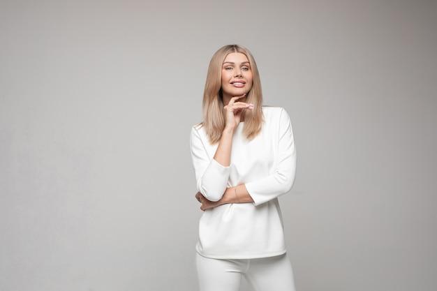 Studio portret van glimlachende blonde aantrekkelijke vrouw in wit pak geïsoleerd op een grijze achtergrond Premium Foto