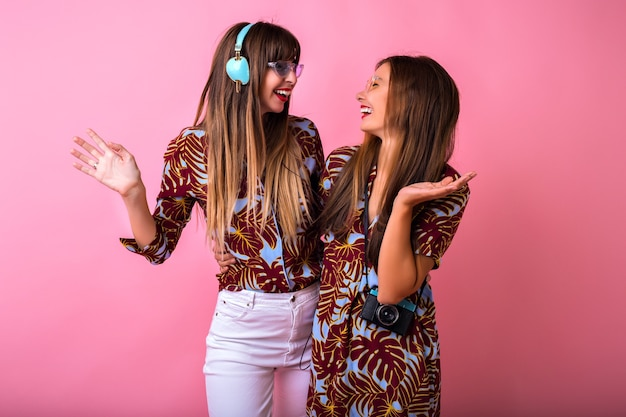 Studio positief beeld van tho mooie beste vrienden vrouw dansen en plezier maken op feestje, schattige verrast emoties, stijlvolle kleur bijpassende kleding, grote koptelefoon en vintage camera. Gratis Foto