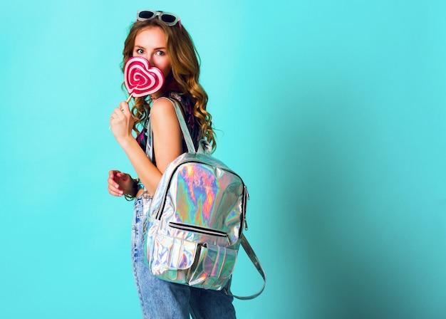 Studio positief portret van het jonge sexy grappige manier gekke vrouw stellen op blauwe muurachtergrond in de uitrusting van de de zomerstijl met roze lolly die drukbovenkant, neonrugzak en leuke glazen dragen. Gratis Foto