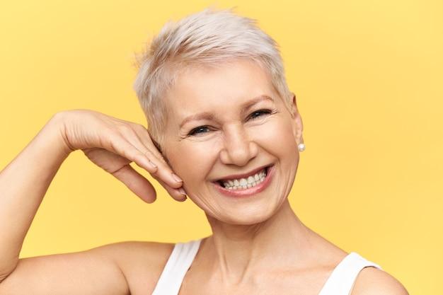 Studio shot van charismatische positieve vrouw van middelbare leeftijd poseren tegen gele achtergrond wang aanraken, camera kijken met brede vrolijke glimlach, verzorgen van haar gerimpelde huid, crème aanbrengen Gratis Foto